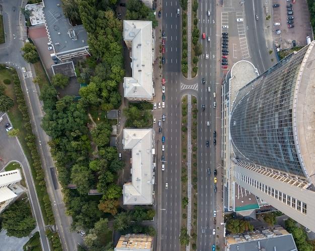 Schieten vanuit de drone strikt boven het moderne kantoorcentrum met weg, auto's, gebouwen en bomen ernaast.
