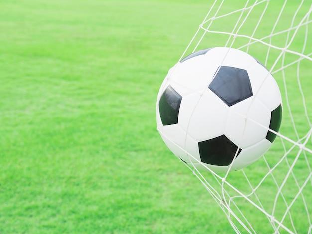 Schietend schot, voetbal in doel netto met de groene achtergrond van het grasgebied