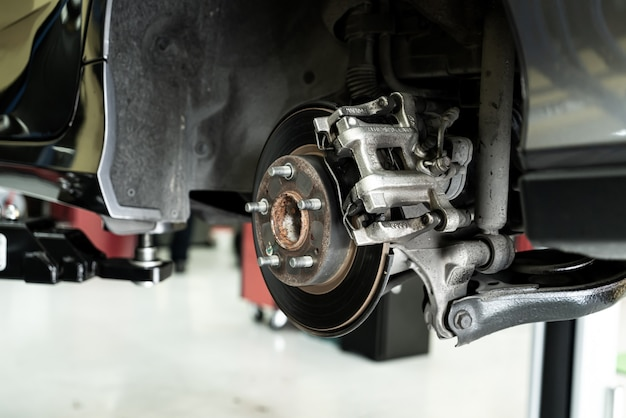 Schijfauto close-up - monteur die auto-onderdelen losschroeft terwijl hij onder een opgeheven auto werkt - autoserviceconcept