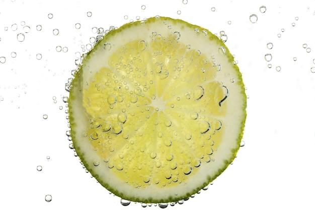 Schijfje limoen in het water met bubbels, geïsoleerd op wit