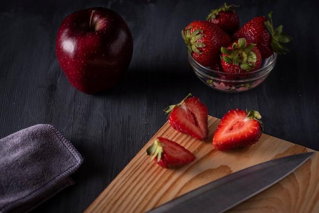 Schijfjes appel en aardbeien op een houten plank