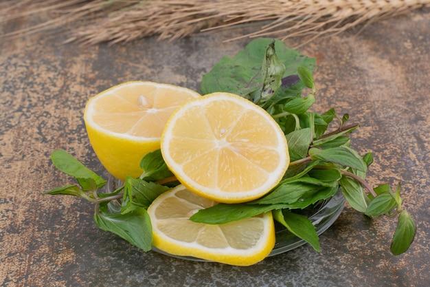 Schijfjes citroen met munt op stenen oppervlak