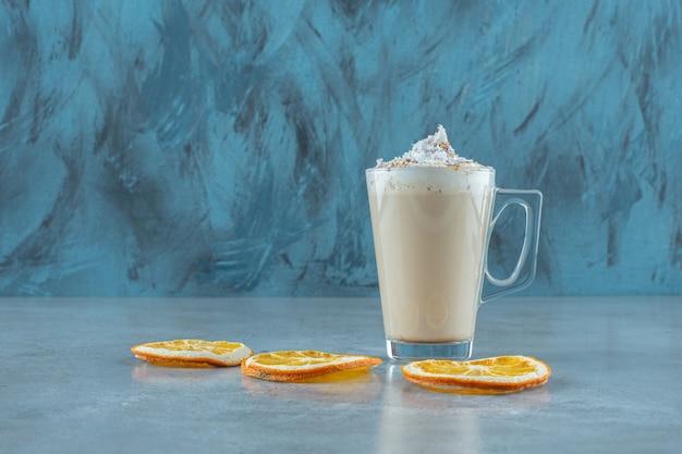 Schijfjes citroen naast een kopje cappuccino, op de blauwe tafel.