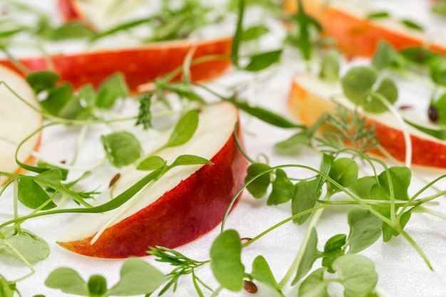 Schijfjes rode appels, jonge microgreen spruiten op witte achtergrond close-up.