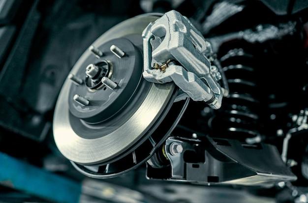 Schijfrem van het voertuig voor reparatie, tijdens het vervangen van nieuwe banden. auto rem repareren in garage. schorsing van auto voor onderhoud remmen en schokdemper systemen. close-up.