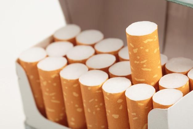 Schil het af sigarettenpakje bereiden roken op witte houten achtergrond. in de rij staan. fotofilters natuurlijk licht.