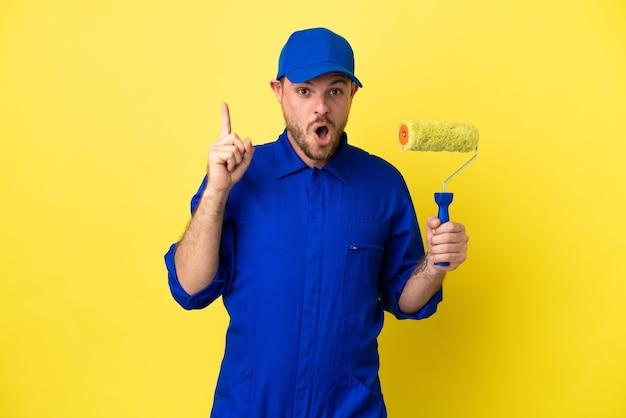 Schilder braziliaanse man geïsoleerd op gele achtergrond met de bedoeling de oplossing te realiseren terwijl hij een vinger optilt