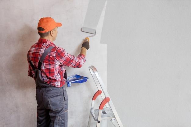Schilder die een muur schildert met verfroller. woondecoratie, reparatieconcept