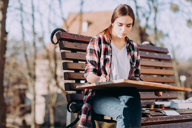Schilder kunstenaar houdt een houten tablet om te schilderen en een penseel in zijn hand