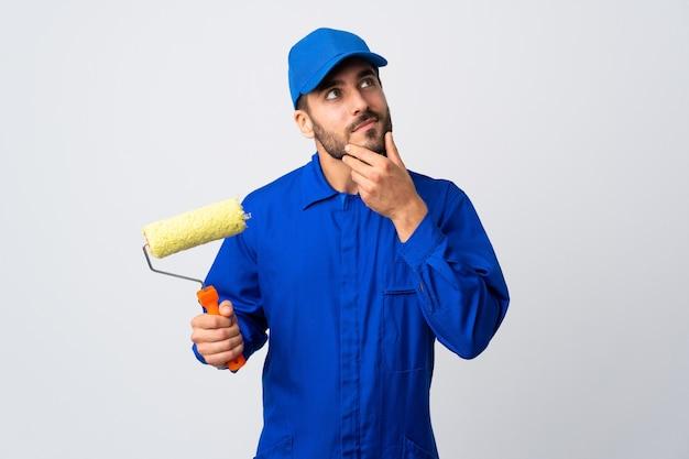 Schilder man met een verfroller geïsoleerd op een witte achtergrond twijfels