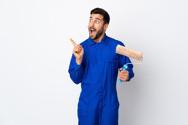 Schilder man met een verfroller geïsoleerd op een witte muur met de bedoeling om de oplossing te realiseren terwijl het opheffen van een vinger