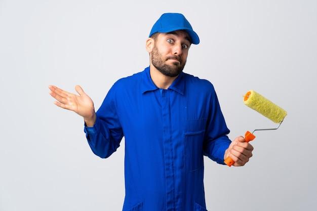 Schilder man met een verfroller geïsoleerd op een witte muur twijfel gebaar maken