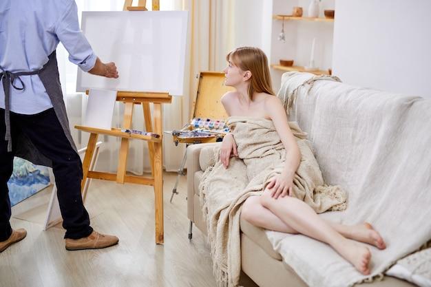 Schilder op de ezel trekt vrouwelijk model zittend op de bank, in lichte studio kamer. kunst concept