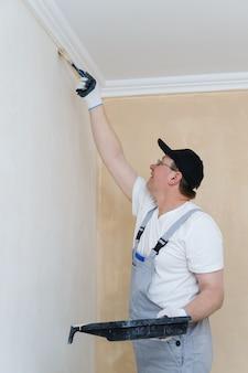 Schilder schildert een muur in de kamer.