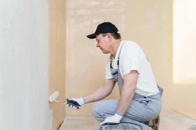 Schilder schildert een muur in de kamer