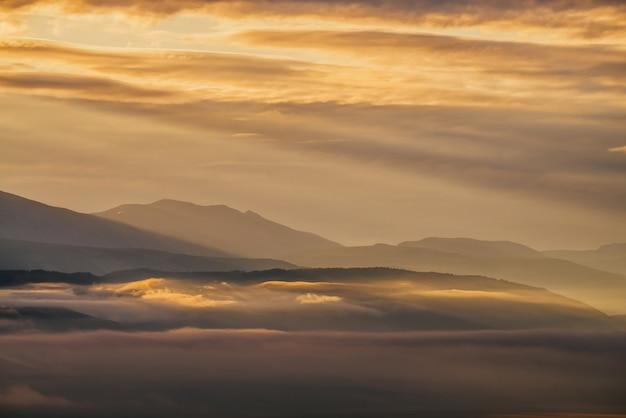 Schilderachtig dageraadberglandschap met gouden lage wolken in vallei tussen bergensilhouetten onder bewolkte hemel. levendig zonsondergang- of zonsopganglandschap met lage wolken in bergdal in verhelderende kleur.