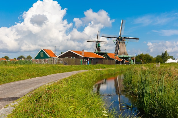 Schilderachtig landelijk landschap met windmolens in zaanse schans dichtbij kanaal, holland, nederland