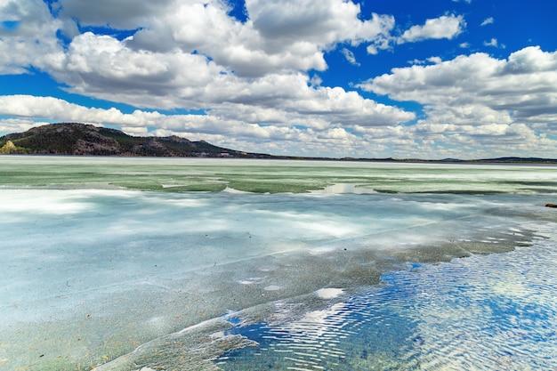 Schilderachtig landschap in burabay national nature park, kazachstan. oever van het grote meer borovoe (burabay) in ijs. wolken worden weerspiegeld in een bevroren meer.