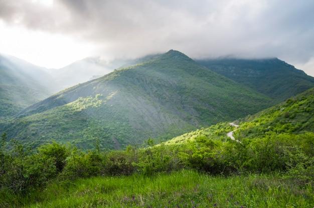 Schilderachtig landschap, regenwolken, bergen bedekt met groene planten, landwegpassen tussen heuvels