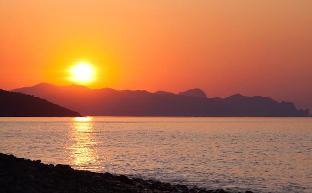 Schilderachtig landschap van kalme zeezon tegen de achtergrond van hoge heuvels of bergen tijdens zomervakantie