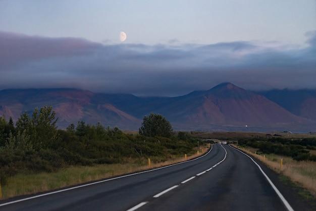 Schilderachtig nachtlandschap met mooie weg, maan en bergen van de westfjord van ijsland.