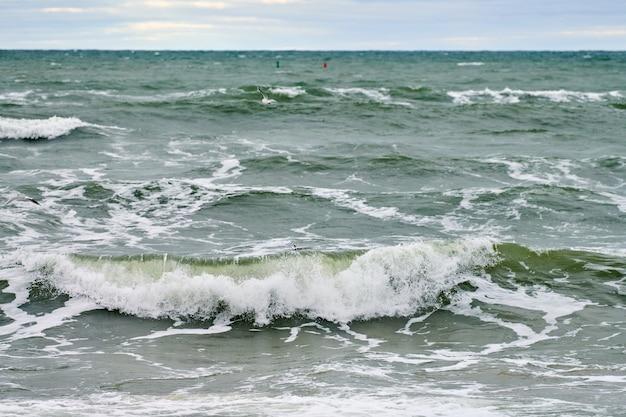 Schilderachtig uitzicht op de blauwe zee met borrelende en schuimende golven en mooie bewolkte hemel