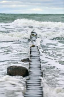 Schilderachtig uitzicht op de blauwe zee met borrelende en schuimende golven. vintage lange houten golfbrekers die zich uitstrekken tot ver naar de zee, winterlandschap van de oostzee. stilte, eenzaamheid, rust en vrede.
