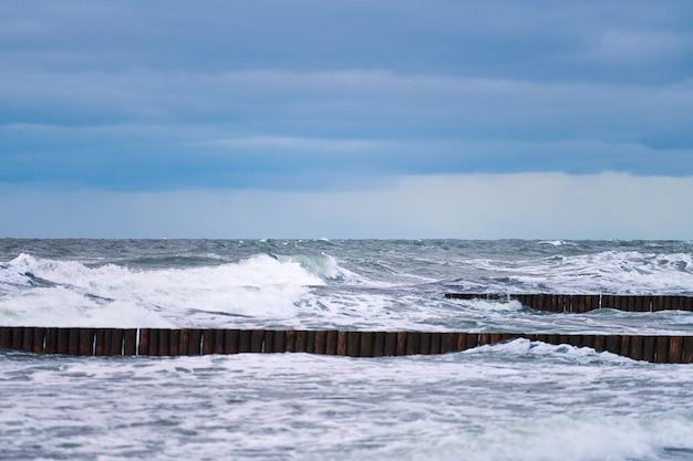 Schilderachtig uitzicht op de blauwe zee met schuimende golven, bewolkte lucht en vintage lange houten golfbrekers die zich uitstrekken tot ver in de zee. winderig weer, mooie avond oostzeelandschap.
