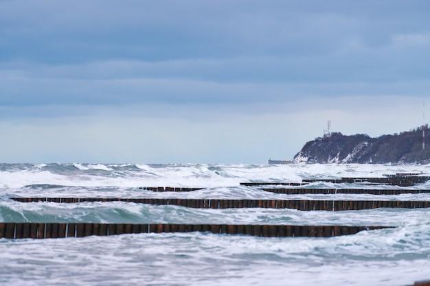 Schilderachtig uitzicht op de blauwe zee met schuimende golven, bewolkte lucht en vintage lange houten golfbrekers die zich uitstrekken tot ver in de zee