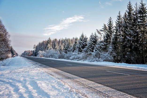 Schilderachtig uitzicht op een winter lege weg met sneeuw, verlicht door de zon.