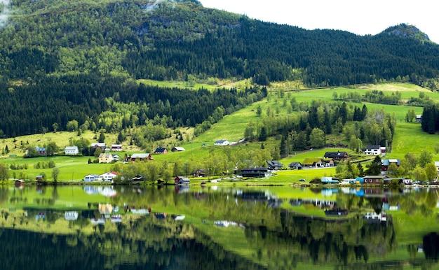 Schilderachtig uitzicht op huizen die reflecteren op een kalm meer in de buurt van een berg in noorwegen