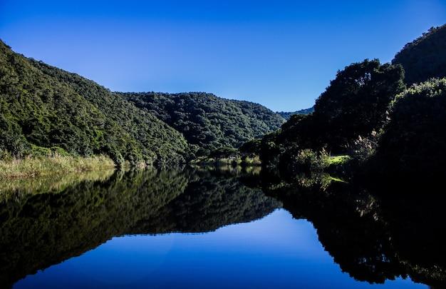 Schilderachtig uitzicht op met groen bedekte bergen en helder meer