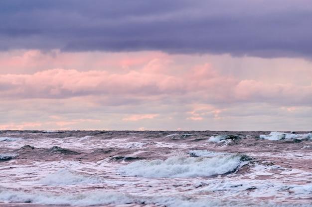 Schilderachtig uitzicht op paarse bewolkte hemel en blauwe zee met schuimende golven