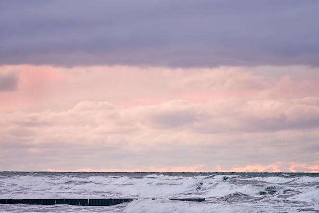 Schilderachtig uitzicht op paarse bewolkte lucht en zee met schuimende golven. vintage lange houten golfbrekers die zich uitstrekken tot ver in de zee. winderig weer, mooie avond oostzeelandschap.