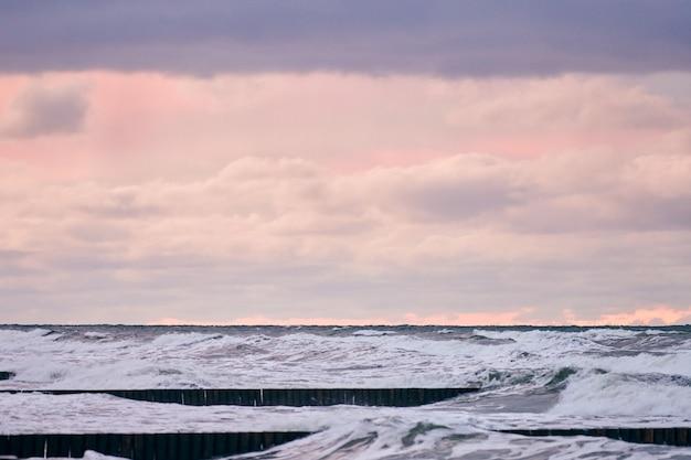 Schilderachtig uitzicht op paarse bewolkte lucht en zee met schuimende golven
