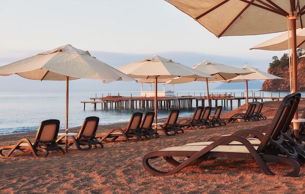 Schilderachtig uitzicht op privé zandstrand op het strand met ligbedden tegen de zee en de bergen. amara dolce vita luxe hotel. toevlucht. tekirova-kemer. kalkoen