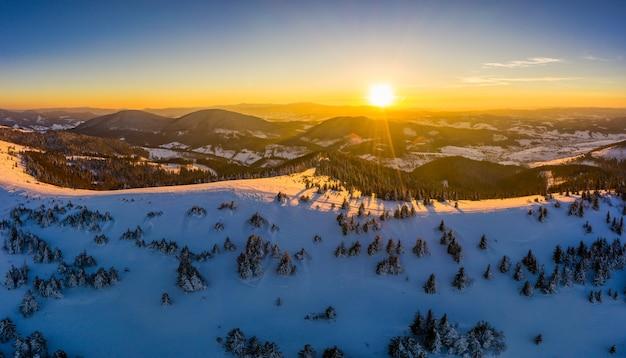 Schilderachtig winterpanorama van bergheuvels bedekt met sneeuw en sparren op een zonnige heldere dag met de zon en de blauwe lucht. ongerept natuurschoonheidsconcept