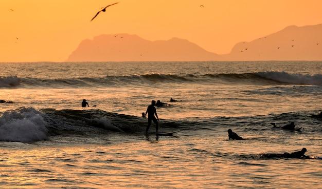 Schilderachtig zonsondergangmoment met silhouetten van surfers en meeuwen op de stille oceaan. lima, peru. zuid-amerika