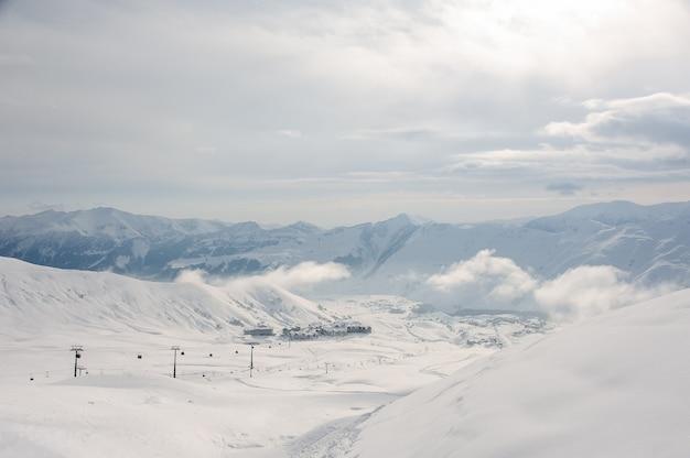 Schilderachtige bovenaanzicht van kabelbaan, kleine huizen en hoge bergen in georgië, gudauri