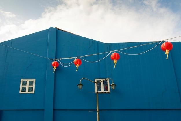 Schilderachtige chinatown-architectuur met felblauwe bouwmuur en rode lantaarnlijn uit singapore