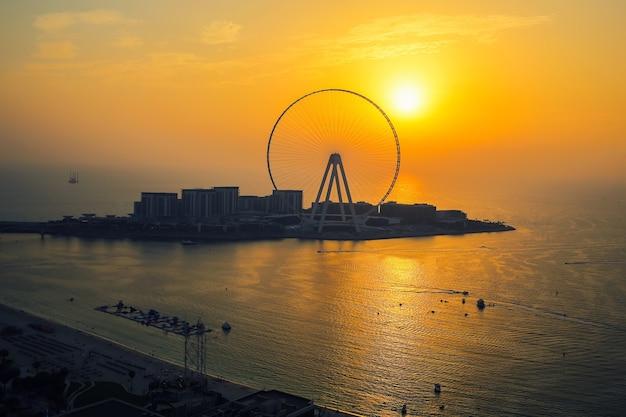 Schilderachtige gele zonsondergang en skyline achter het reuzenrad van dubai eye en bluewaters-eiland