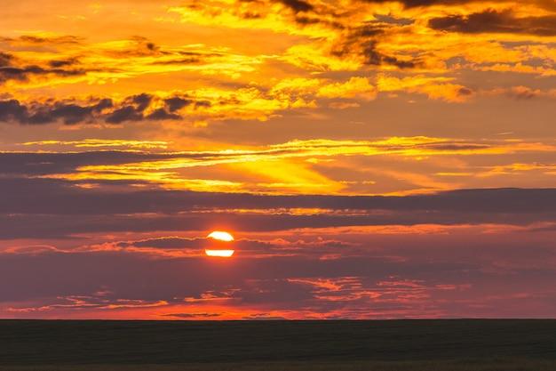 Schilderachtige hemel met wolken tijdens de zonsondergang in het veld