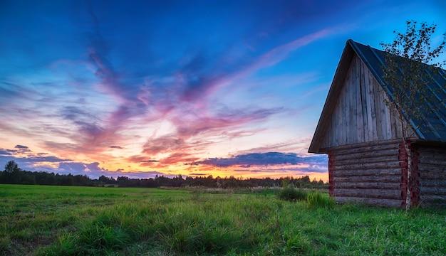 Schilderachtige landelijke zonsondergang. skyline met blokhut op de voorgrond.