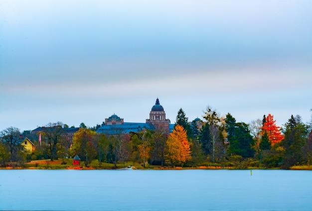 Schilderachtige landschapsmening van herfstbladeren aan bomen met een oud gebouw