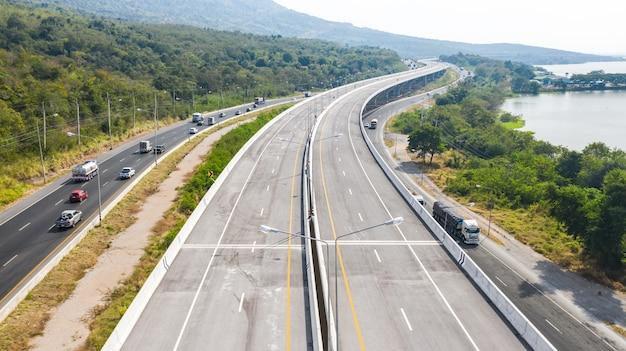 Schilderachtige luchtfoto van grote snelweg, bovenaanzicht van drone van weg en groen bos berg in thailand