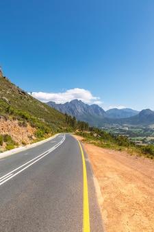Schilderachtige weg in franschhoek vallei met zijn beroemde wijnmakerijen en omliggende bergen, zuid-afrika