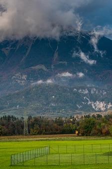 Schilderachtige wolken op bergen met wegen en rails in de. herfst bos en groen gras weide aan de voorkant