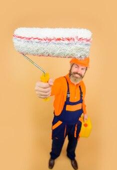 Schilderconcept bebaarde man in werkkleding met verfroller bebaarde reparateur in uniforme greep