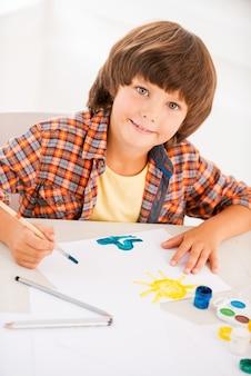 Schilderen. bovenaanzicht van kleine jongen die ontspant tijdens het schilderen met aquarellen aan tafel