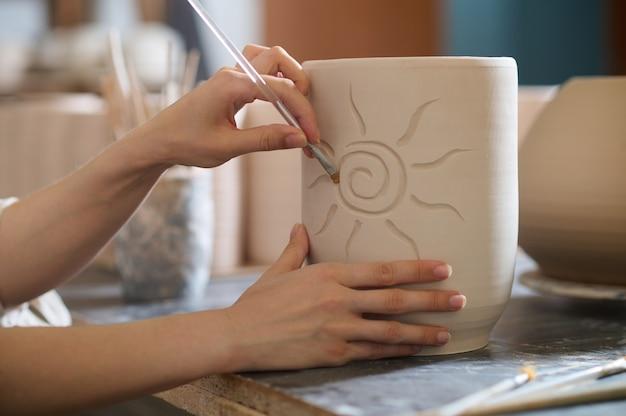 Schilderen. close-up van handen met een penseel op een kopje